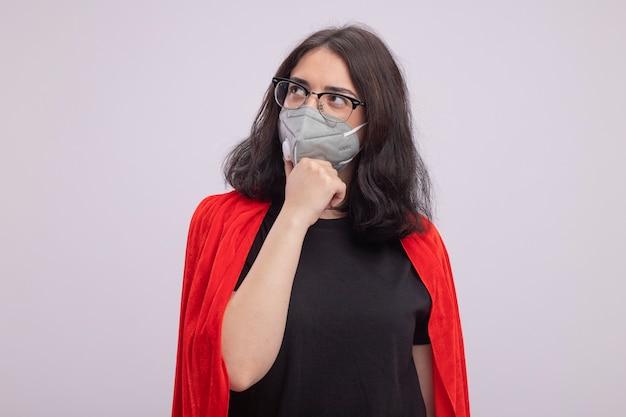 Jovem super-heroína caucasiana pensativa com capa vermelha usando óculos e máscara protetora, segurando o queixo, olhando para o lado isolado na parede branca com espaço de cópia