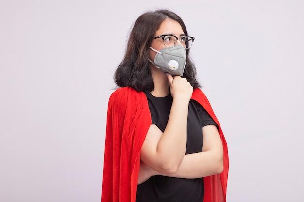 Jovem super-heroína caucasiana pensativa com capa vermelha, usando óculos e máscara protetora, tocando o queixo, olhando para o lado isolado na parede branca com espaço de cópia