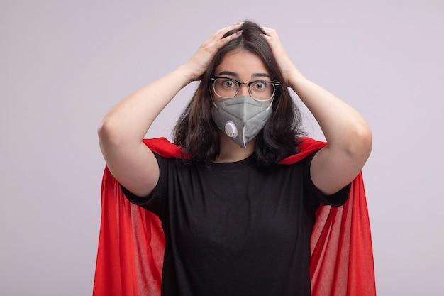 Jovem super-heroína caucasiana preocupada com capa vermelha usando óculos e máscara protetora, mantendo as mãos na cabeça