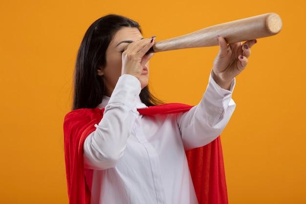 Jovem super-heroína caucasiana segurando taco de beisebol e usando-o como telescópio isolado em fundo laranja