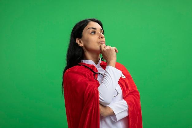 Jovem super-heroína confiante olhando para o lado, vestindo bata médica com estetoscópio agarrado no queixo isolado no verde