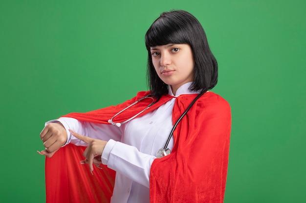 Jovem super-heroína confiante usando estetoscópio com manto médico e capa mostrando o gesto do relógio de pulso isolado na parede verde
