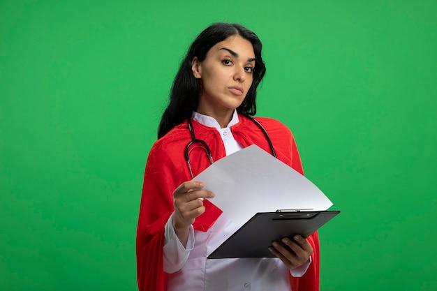 Jovem super-heroína confiante vestindo túnica médica com estetoscópio segurando uma prancheta, folheando isolado em verde