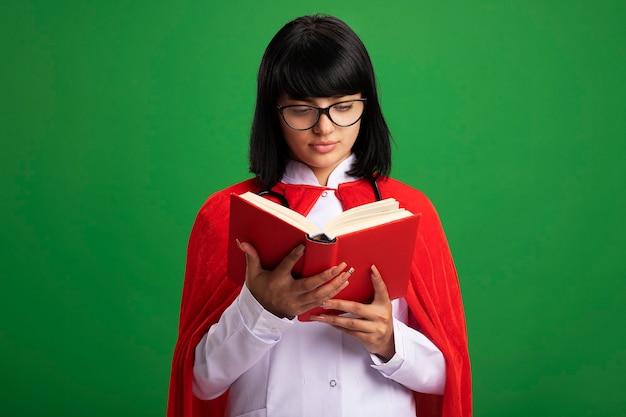 Jovem super-heroína pensando usando estetoscópio com manto médico e capa com óculos segurando e olhando para um livro
