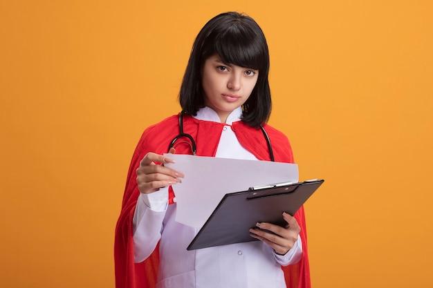 Jovem super-heroína procurando usando estetoscópio com manto médico e capa folheando a prancheta isolada na parede laranja