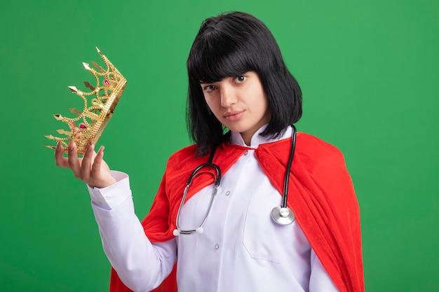 Jovem super-heroína satisfeita usando estetoscópio com manto médico e capa segurando uma coroa isolada na parede verde