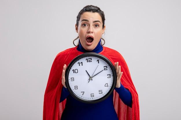 Jovem super-heroína surpresa segurando um relógio de parede isolado no fundo branco