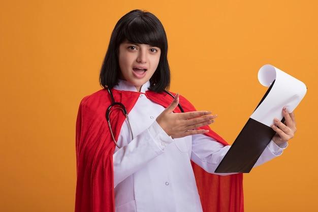 Jovem super-heroína surpresa usando estetoscópio, manto médico e capa folheando a prancheta