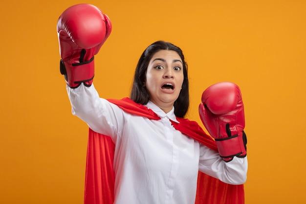 Jovem supermulher assustada usando luvas de boxe olhando para frente levantando as mãos isoladas na parede laranja