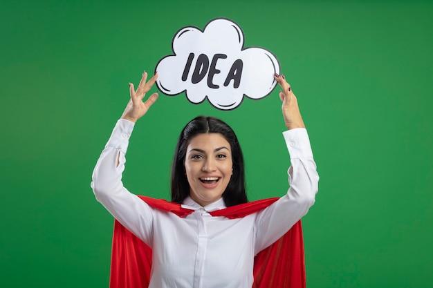 Jovem supermulher brincalhona levantando uma bolha de ideia acima da cabeça com a boca aberta olhando para frente isolada na parede verde