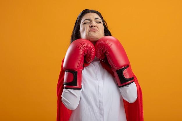Jovem supermulher carrancuda usando luvas de boxe mantendo as mãos embaixo do queixo com os olhos fechados, isolados na parede laranja