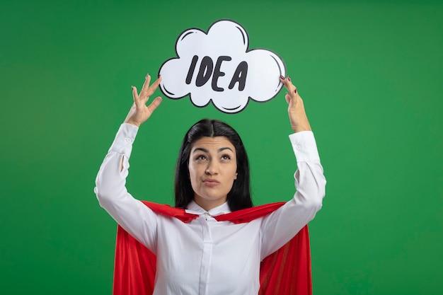 Jovem supermulher levantando uma bolha de ideia acima da cabeça, olhando em dúvida, isolada na parede verde