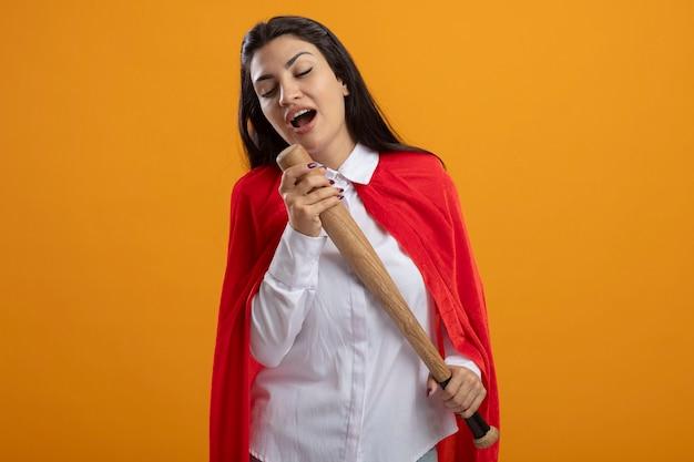 Jovem supermulher segurando um taco de beisebol cantando com os olhos fechados usando o taco de beisebol como microfone isolado na parede laranja