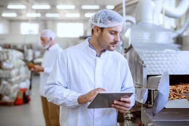 Jovem supervisor sério caucasiano avaliando a qualidade dos alimentos na fábrica de alimentos enquanto segura o tablet. o homem está vestido com uniforme branco e tem rede para o cabelo.