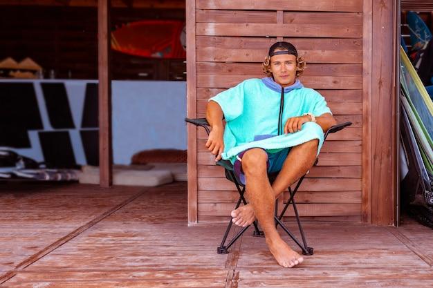 Jovem surfista atraente vestindo um roupão de banho está sentado no terraço à beira-mar, relaxando e olhando para a distância no mar
