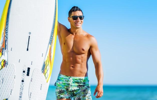 Jovem surfista bonito com prancha na praia num dia ensolarado de verão