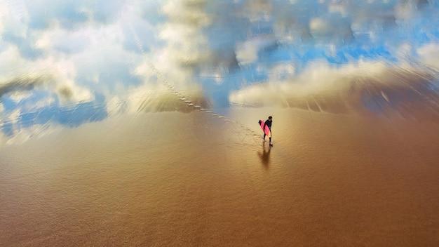 Jovem surfista caminhando em uma praia arenosa