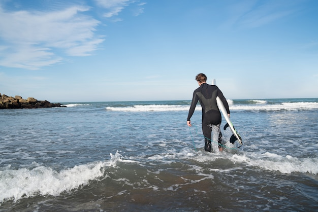 Jovem surfista entrando na água com sua prancha de surf em um terno preto. esporte e conceito de esporte aquático.