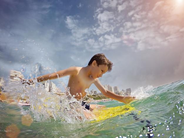 Jovem surfista, garoto feliz no oceano na prancha de surf