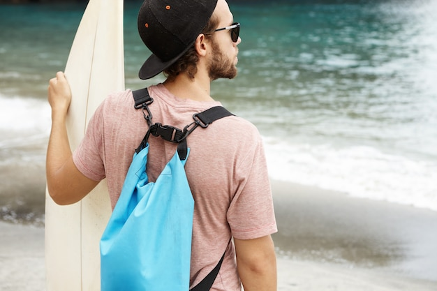 Jovem surfista iniciante caucasiano com barba em frente ao oceano azul e esperando seu instrutor de surf