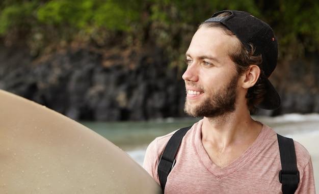 Jovem surfista iniciante com um boné de beisebol virado para trás, olhando para o mar com um sorriso feliz e inspirado