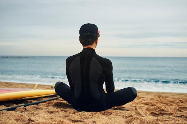 Jovem surfista na praia com boné