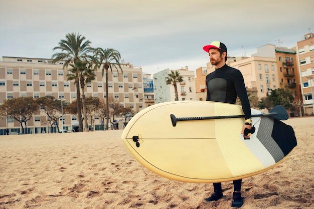 Jovem surfista na praia com prancha de surf
