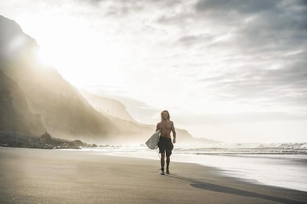 Jovem surfista na praia tropical ao pôr do sol - cara de homem com sua prancha de surf andando ao lado do oceano em dia ensolarado - conceito de esporte radical - foco no corpo masculino