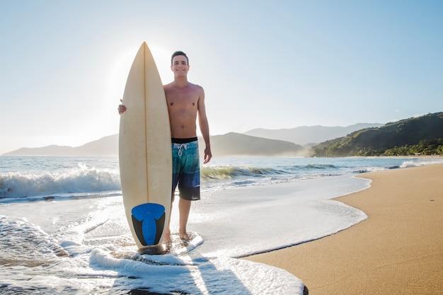 Jovem surfista na praia
