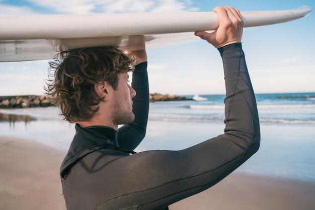 Jovem surfista segurando sua prancha de surf.