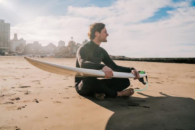Jovem surfista sentado na praia, olhando para o oceano com sua prancha de surf. esporte e conceito de esporte aquático.