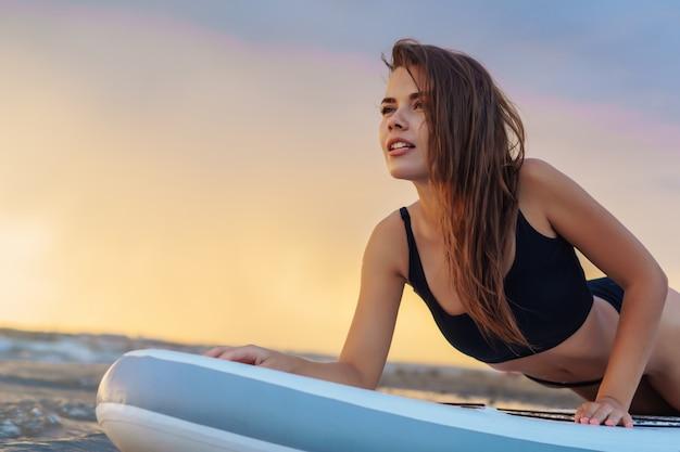 Jovem surfista sexy mulher deitada na prancha sup olhando para o pôr do sol.