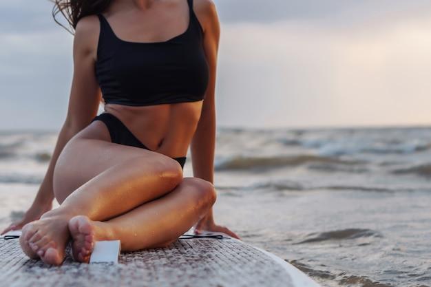 Jovem surfista sexy mulher sentada no seu sup board olhando para o pôr do sol.