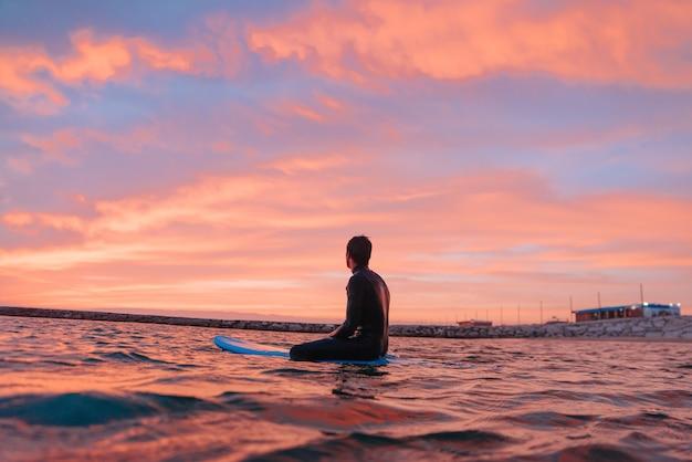 Jovem surfista surfando ao pôr do sol