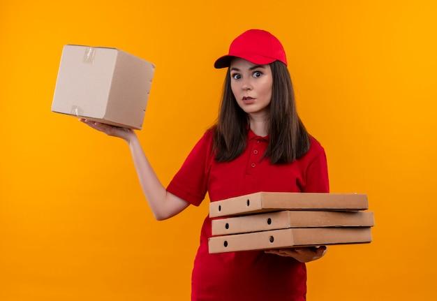 Jovem surpreendeu a entregadora de camiseta vermelha com tampa vermelha segurando uma caixa e uma caixa de pizza em um fundo amarelo isolado