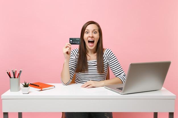 Jovem surpreendeu a mulher animada com a boca aberta segurando um cartão de crédito enquanto trabalhava sentado no escritório com o laptop