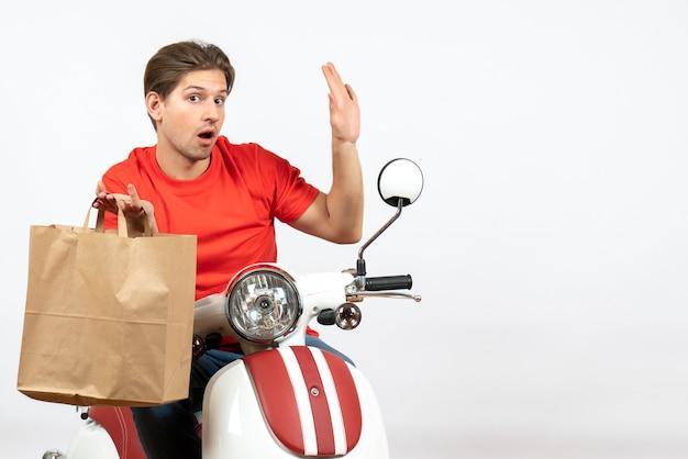 Jovem surpreendeu o entregador de uniforme vermelho sentado na scooter segurando um saco de papel e mostrando cinco na parede branca