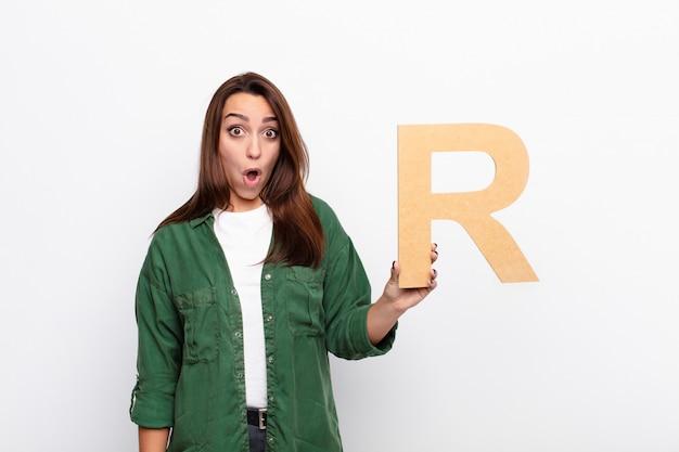 Jovem surpreendida, chocada, espantada, segurando a letra r do alfabeto para formar uma palavra ou uma frase.
