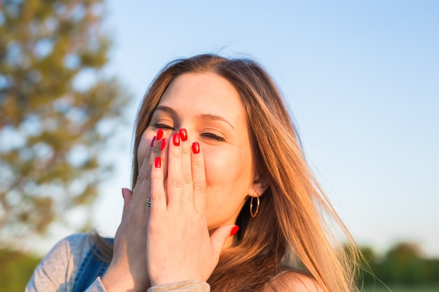 Jovem surpreendida, cobrindo a boca com as mãos ao ar livre.