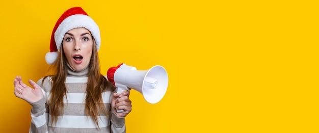 Jovem surpreendida com chapéu de papai noel com um megafone em um fundo amarelo. bandeira.