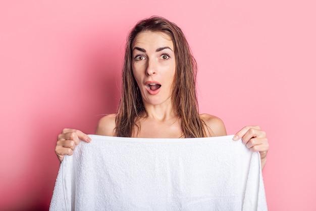 Jovem surpreendida com o cabelo molhado nu, se escondendo atrás da toalha no fundo rosa.