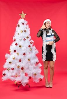 Jovem surpreendida com um chapéu de papai noel e perto de uma árvore de natal decorada segurando presentes e fazendo um gesto de chamada