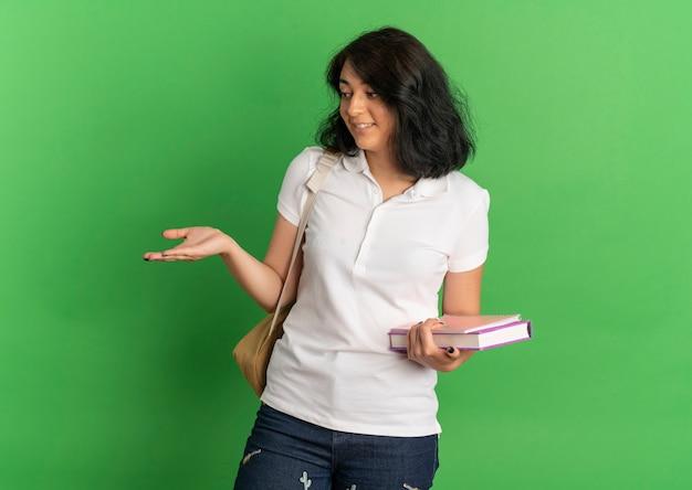 Jovem surpreendida com uma aluna bonita caucasiana usando uma bolsa traseira segurando livros, olhando e apontando com a mão ao lado no verde com espaço para cópia