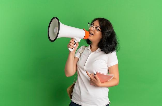 Jovem surpreendida com uma colegial muito caucasiana de óculos e bolsa traseira fala pelo alto-falante segurando um caderno isolado em um espaço verde com espaço de cópia