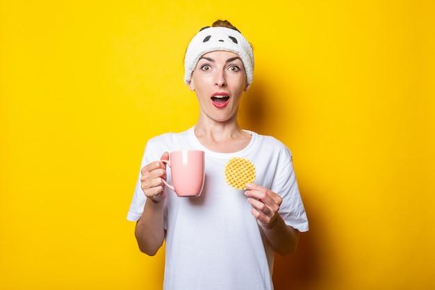 Jovem surpreendida com uma xícara de café e um waffle belga em um fundo amarelo