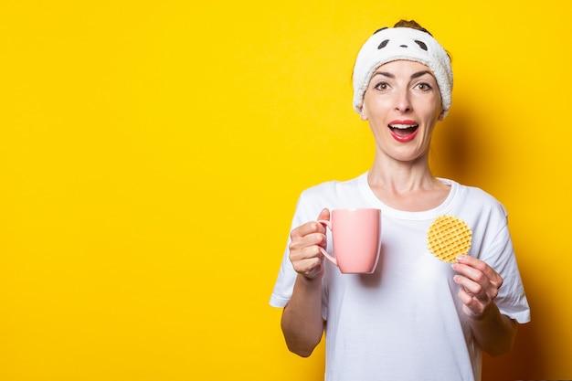Jovem surpreendida com uma xícara de chá e waffle belga em fundo amarelo.