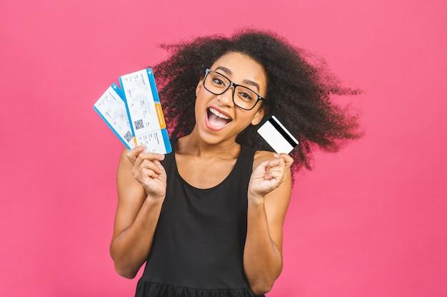 Jovem surpreendida em casual em rosa no estúdio. simule o espaço da cópia. segurando cartão de crédito, bilhetes de cartão de embarque.