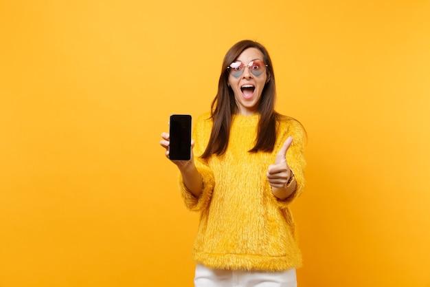 Jovem surpreendida em copos de coração aparecendo o polegar, segurando o telefone móvel com tela vazia preta em branco, isolada no fundo amarelo brilhante. pessoas sinceras emoções, estilo de vida. área de publicidade.