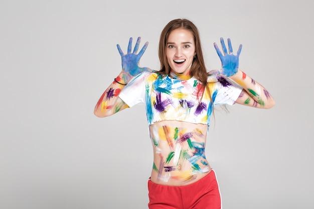 Jovem surpreendida está suja de tinta multicolorida.