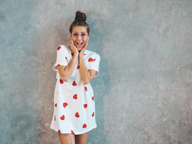 Jovem surpreendida linda olhando com as mãos perto da boca. menina na moda em vestido de verão casual branco.